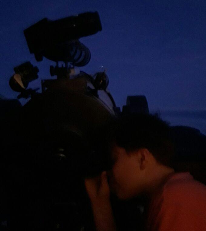Teleskop rettet imod Jupiter. Børn kigger igennem det.